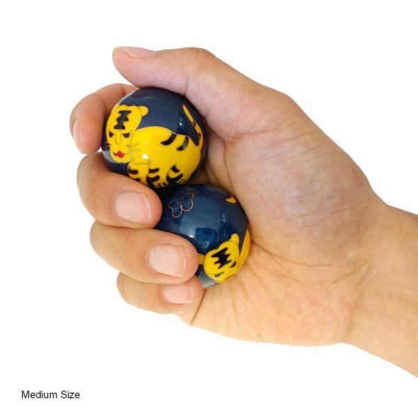 Hand holding medium tiger baoding balls