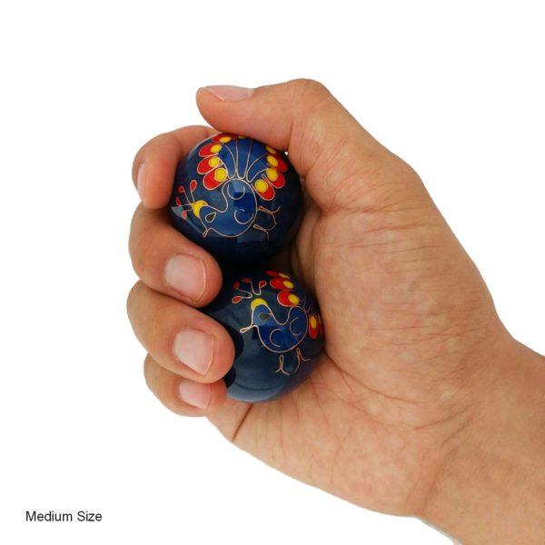 Hand holding medium size peacock baoding balls
