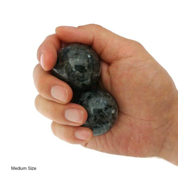 Hand holding medium larvikite baoding balls