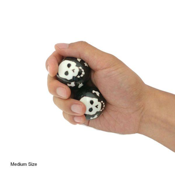 Hand holding medium skull and bones baoding balls